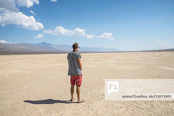 Junger Mann schaut in die weite Landschaft  ausgetrockneter Boden mit Rissen  Death Valley  Death-Valley-Nationalpark  Kalifornien  USA  Nordamerika