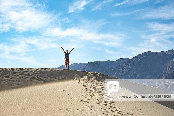 Junger Mann steht auf einer Sanddüne  Mesquite Flat Sand Dunes  Death Valley  Death-Valley-Nationalpark  Kalifornien  USA  Nordamerika