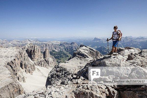 Bergsteigerin beim Aufstieg auf den Piz Boé über den Vallonsteig in der Sellagruppe  hinten das Gadertal mit dem Heiligkreuzkofel und der Conturinesgruppe  links die Puezgruppe  Klettersteig  Dolomiten  Corvara  Gadertal  Südtirol  Trentino-Südtirol  Italien  Europa