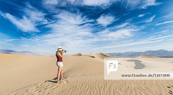 Touristin fotografiert  Mesquite Flat Sand Dunes  Sanddünen  hinten Ausläufer der Amargosa-Range Bergkette  Death Valley  Death-Valley-Nationalpark  Kalifornien  USA  Nordamerika