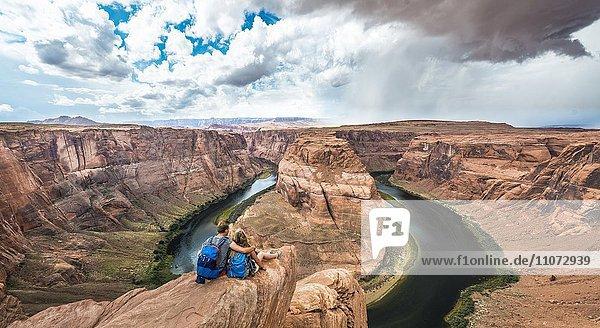 Junges Pärchen sitzt auf einem Felsen und schaut über das Horseshoe Bend,  Flussschleife des Colorado River,  King Bend,  Glen Canyon National Recreation Area,  Page,  Arizona,  USA,  Nordamerika