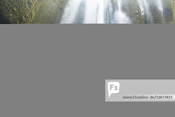 Wanderer auf Felsen vor Wasserfall Gljufrabui  bei Hamragardar  Südisland  Island  Europa