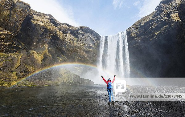 Wanderer mit ausgestreckten Armen vor Wasserfall Skogafoss mit Regenbogen  Skogar  Süd Island  Island  Europa