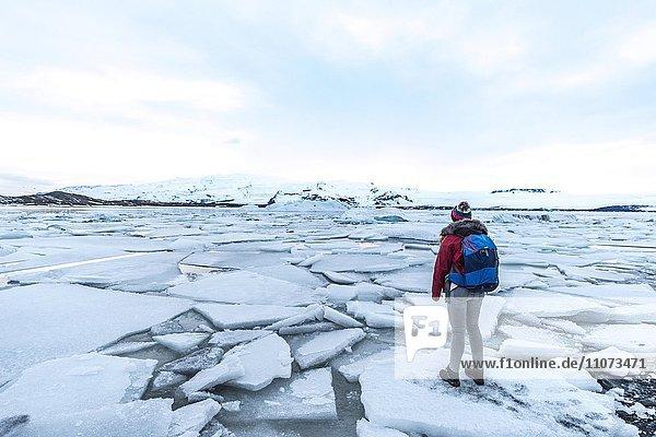 Frau steht auf Eisscholle  Gletscher Lagune Jökulsárlón  Gletschersee  Südrand des Vatnajökull  Südostisland  Island  Europa