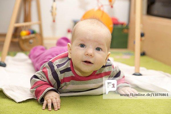 Baby  4 Monate  liegt auf dem Bauch mit erhobenem Kopf