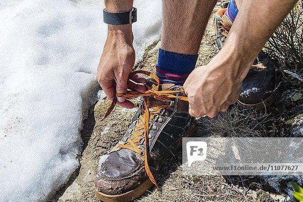 Junger Mann  Wanderer bindet Wanderschuhe  Symbolbild Wandern  Schladming  Steiermark  Österreich  Europa