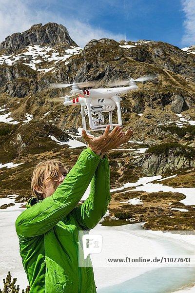 Junger Mann fängt eine Drohne im GEbirge  Rohrmoos-Untertal  Schladminger Tauern  Schladming  Steiermark  Österreich  Europa