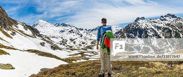Junger Mann,  Wanderer schaut in die Ferne,  Berglandschaft mit Schneeresten,  Rohrmoos-Untertal,  Schladminger Tauern,  Schladming,  Steiermark,  Österreich,  Europa
