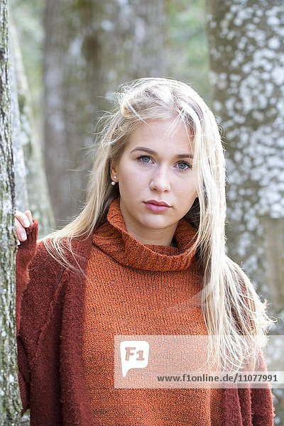 Young girl with long blond hair leaning on a tree