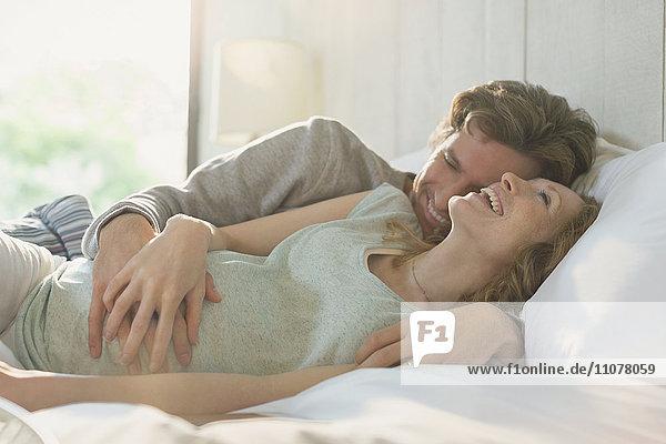 Liebevolles schwangeres Paar  das im Bett liegt und lacht.