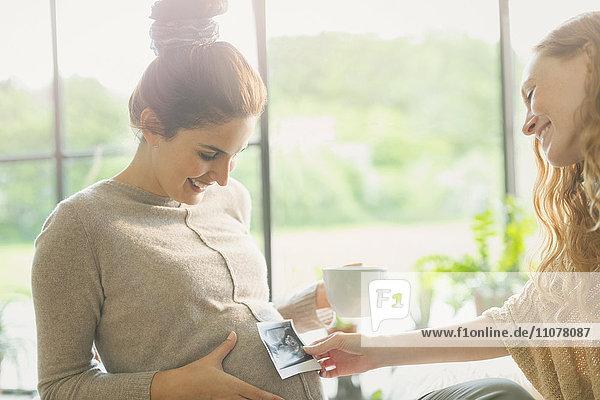 Freund hält Ultraschall an den Bauch einer schwangeren Frau.