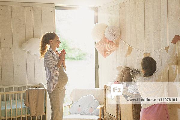 Schwangere Mutter und Tochter schmücken sonnigen Kindergarten