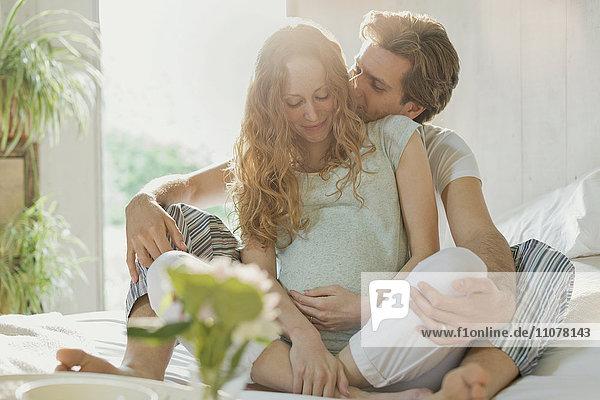 Zärtliches  schwangeres Paar im Schlafanzug auf dem Bett in einem sonnigen Schlafzimmer Zärtliches, schwangeres Paar im Schlafanzug auf dem Bett in einem sonnigen Schlafzimmer