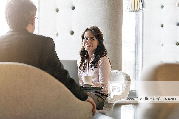 Lächelnde Geschäftsfrau  die dem Geschäftsmann in der Lobby zuhört.