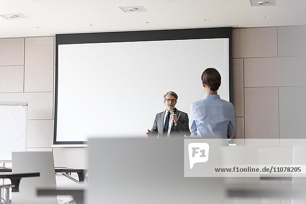 Geschäftsmann mit Mikrofon spricht mit Geschäftsfrau im Konferenzraum