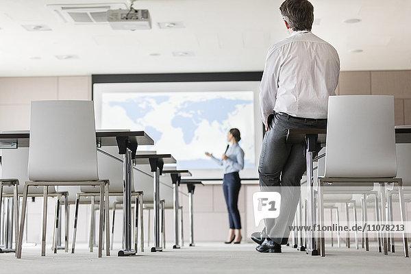 Geschäftsmann beobachtet Geschäftsfrau bei der Präsentation auf der Projektionswand im Konferenzraum