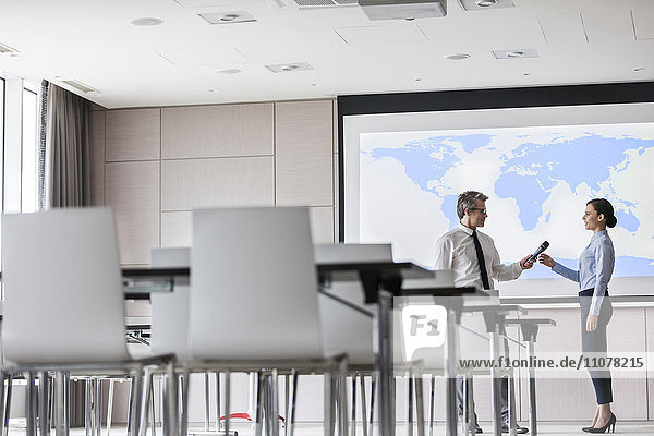 Geschäftsmann übergibt Mikrofon an Geschäftsfrau an der Projektionswand im Konferenzraum