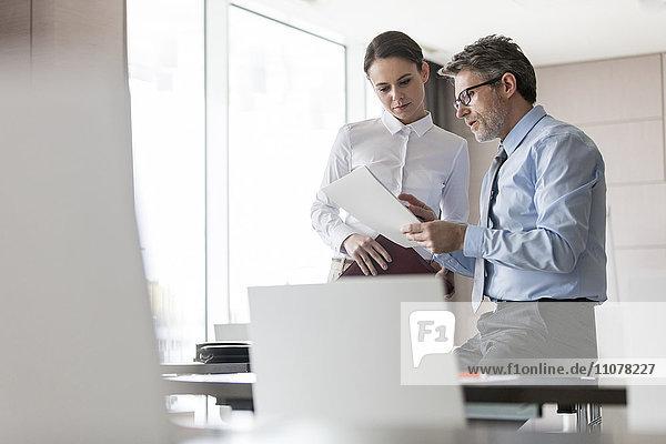 Geschäftsmann und Geschäftsfrau bei der Prüfung von Unterlagen