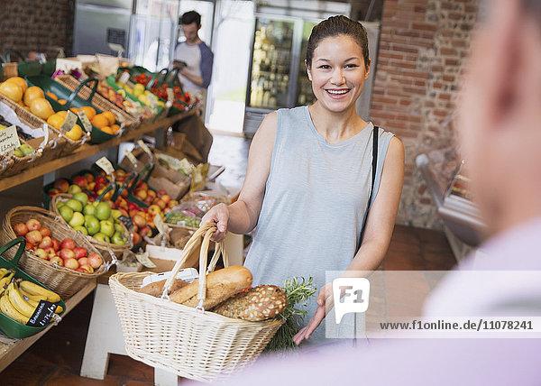Frau mit Korb lächelt Lebensmittelhändlerin an