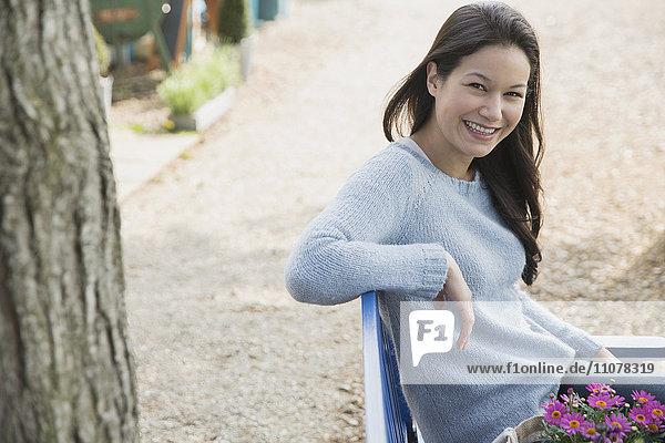 Portrait lächelnde Frau sitzend auf Bank mit Blumen