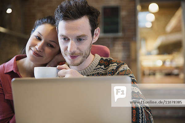 Couple drinking coffee and using laptop in cafe