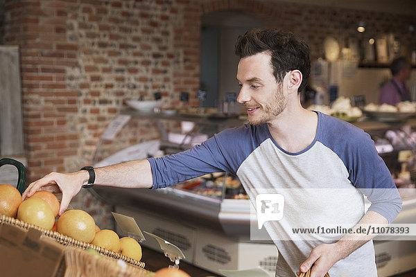 Mann  der auf dem Markt nach Orangen greift. Mann, der auf dem Markt nach Orangen greift.