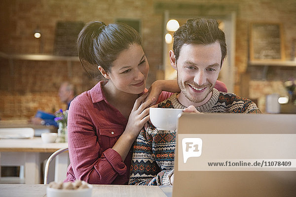 Smiling couple drinking coffee using laptop at cafe