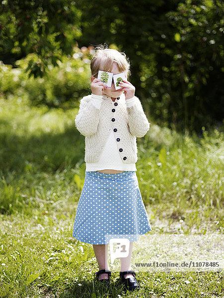 Girl peeking through photographs