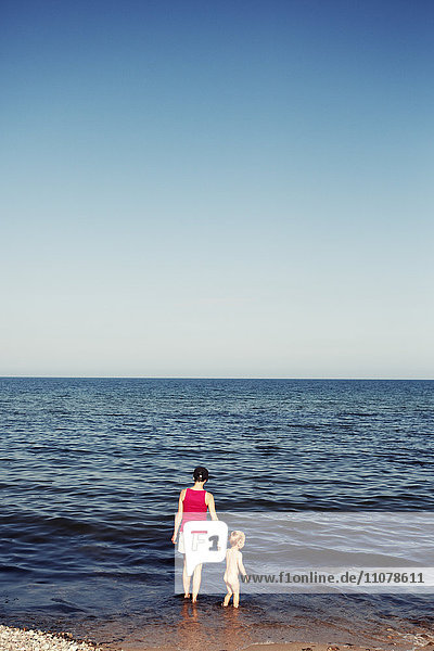 Mother and son standing in sea