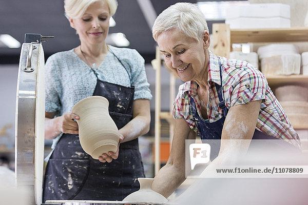 Seniorin mit Töpferei am Ofen im Atelier
