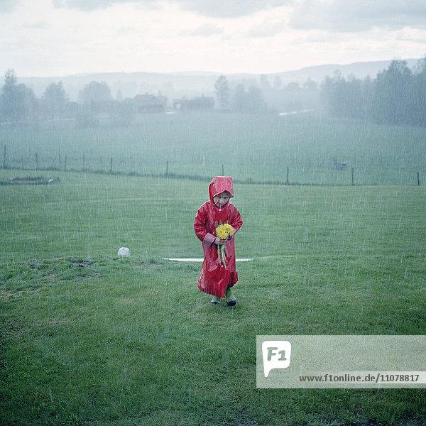 Girl in raincoat walking through meadow during rain