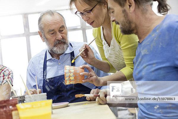 Lehrer und reife Schüler malen Töpferei im Atelier
