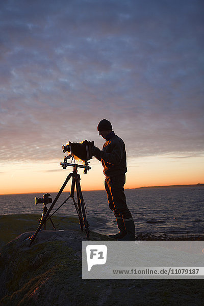 Silhouette of man standing by sea with camera at dusk  side view