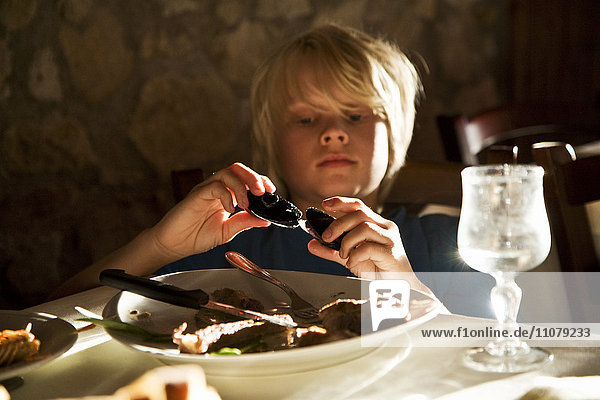 Boy eating mussels in restaurant