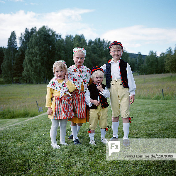 Children in traditional clothing standing on grass field  portrait