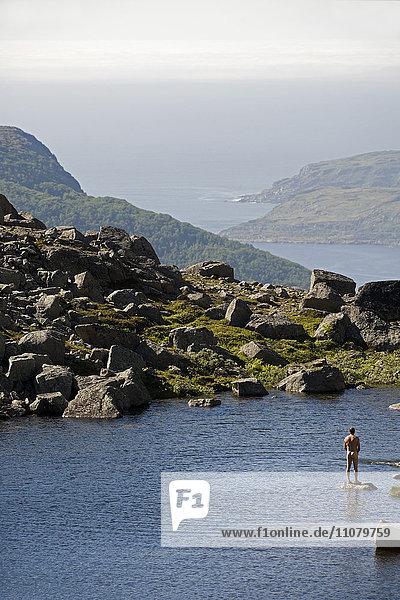 Man standing at mountain lake