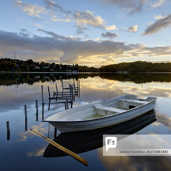 Rowboat floating on lake at sunset