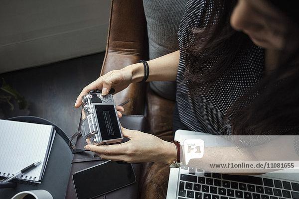 Abgeschnittenes Bild eines Bloggers mit Kamera im Büro