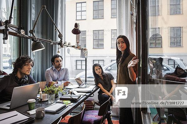 Kreative Geschäftsfrau bei der Präsentation vor Kollegen im modernen Büro