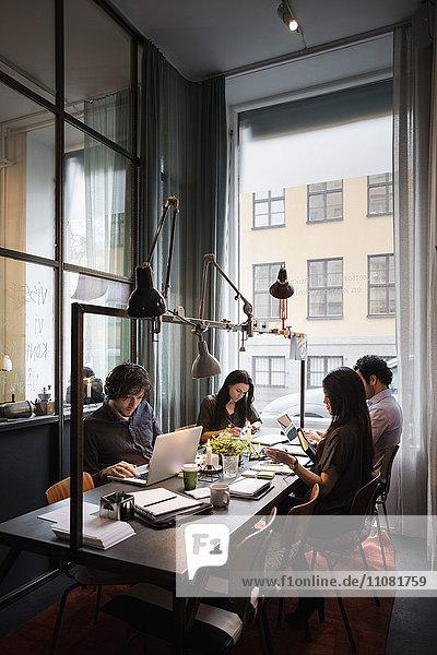 Kreatives Business-Team am Tisch bei der Arbeit im modernen Büro