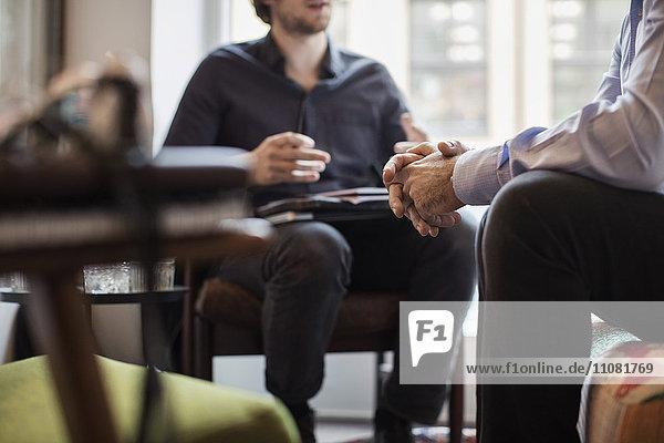 Mittelteil der Geschäftsleute  die während ihrer Amtszeit diskutieren