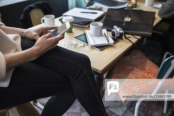 Mittelteil der Geschäftsfrau mit Smartphone am Tisch im Kreativbüro
