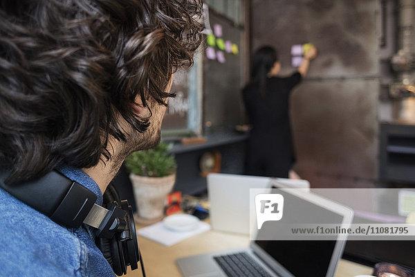 Mittelteil des kreativen Geschäftsmannes beim Anblick einer Mitarbeiterin  die Haftnotiz an die Wand klebt.