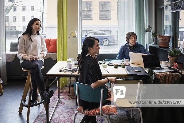 Blogger sitzen am Tisch  während sie im Kreativbüro zuhören.