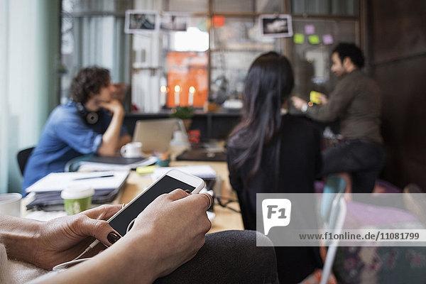Nahaufnahme einer Frau  die ihr Handy gegen Kollegen aus dem Kreativbüro hält