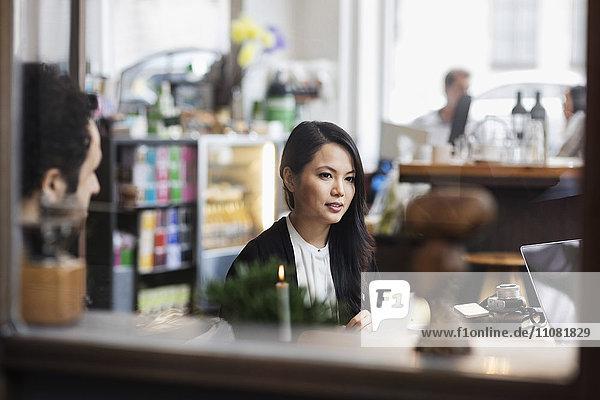 Geschäftsfrau und Mitarbeiterin in der Besprechung gesehen durch Glas im Kreativbüro