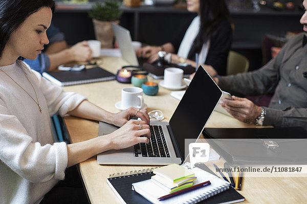 Frau mit Laptop im Sitzen mit Kollegen am Tisch