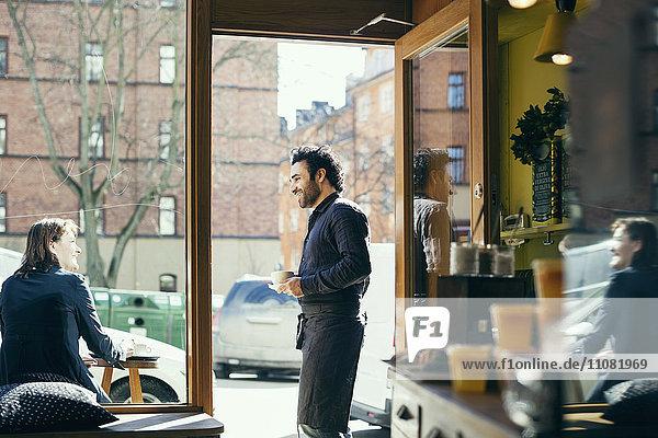 Lächelnder Kellner im Gespräch mit einer Frau auf dem Bürgersteig durch Glas im Café gesehen