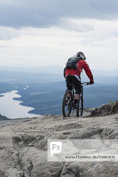Rückansicht des Mountainbikers auf dem Felsen gegen den Himmel