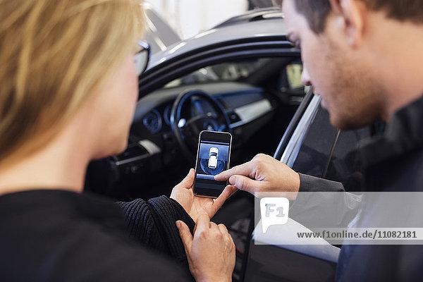 Hochwinkelansicht des Mechanikers  der dem Kunden die mobile Anwendung erklärt.